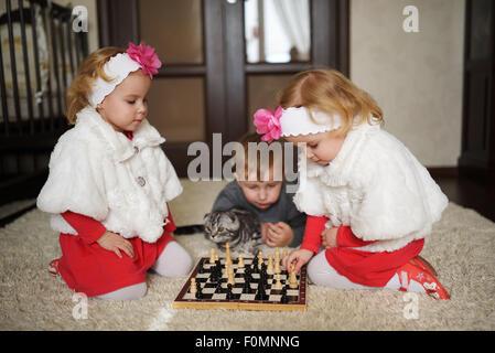 Kinder spielen Schach am Boden liegend - Stockfoto