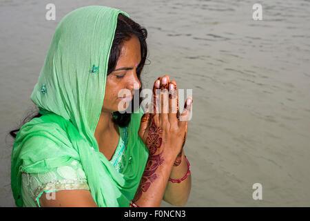 Eine junge Frau mit langen schwarzen Haaren, Henna bemalte Hände und ein grünes Kleid ist an den Ghats von dem heiligen - Stockfoto