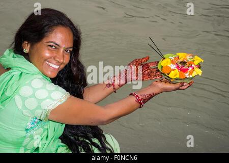 Eine junge Frau mit langen schwarzen Haaren, Henna bemalte Hände und ein grünes Kleid hält eine Deepak, eine Blume - Stockfoto