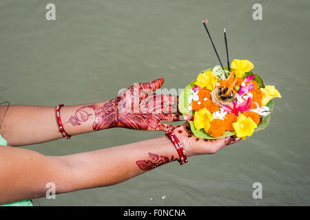 Ein paar Henna bemalte Hände halten Deepak, eine Blume bietet an den Ghats von dem heiligen Fluss Ganges, Rishikesh - Stockfoto