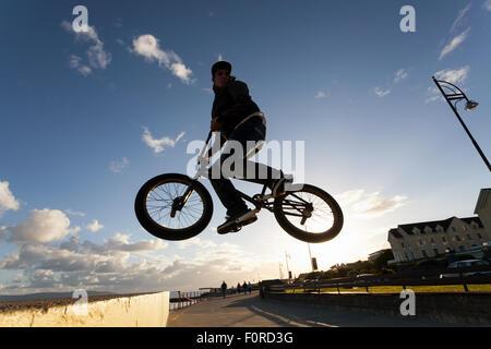 Junger Mann führt BMX Stunts während des Sonnenuntergangs an der Straße. - Stockfoto