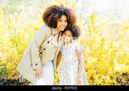 Porträt der Mutter Arm um Tochter, Blick in die Kamera, Lächeln - Stockfoto