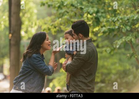 Seitenansicht von Mutter und Vater weht Kuss Baby jungen - Stockfoto