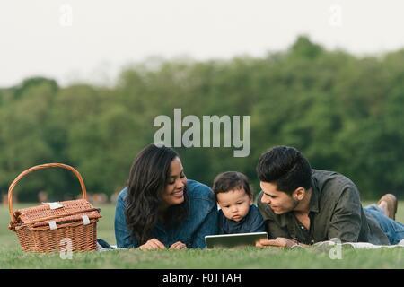 Mutter, Vater und Baby Boy Handauflegen Fronten im Freien mit digital-Tablette - Stockfoto