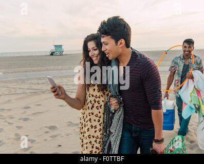 Gruppe von Freunden zu Fuß am Strand, junge Paar Smartphone betrachten