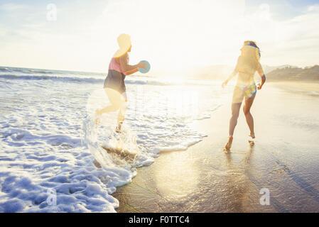 Junges Paar herumalbern auf Strand, Meer, Sonnenuntergang - Stockfoto