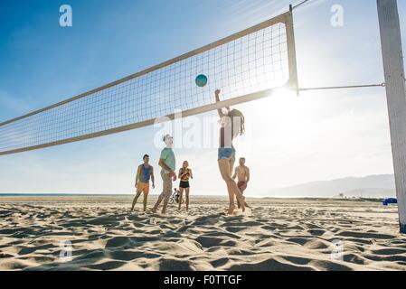 Gruppe von Freunden, die am Strand Volleyball spielen - Stockfoto