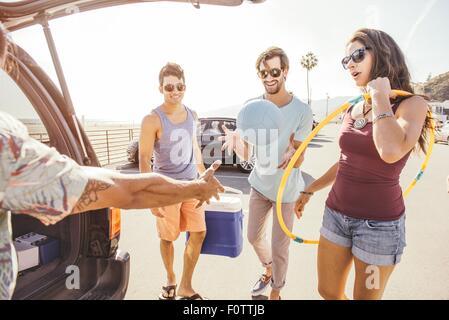Gruppe von Freunden mit dem Auto stehen, Picknick und spielen Elemente halten - Stockfoto
