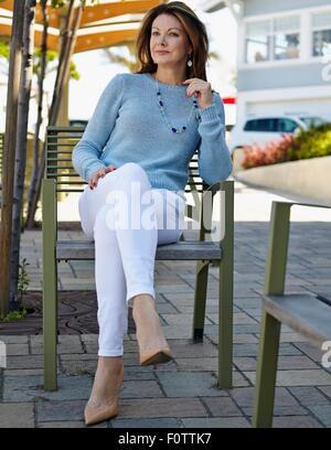 Porträt der elegante Reife Frau auf Terrasse Stuhl sitzend - Stockfoto