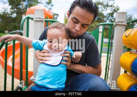 Junger Mann guiding Kleinkind Bruder auf Rutschbahn - Stockfoto