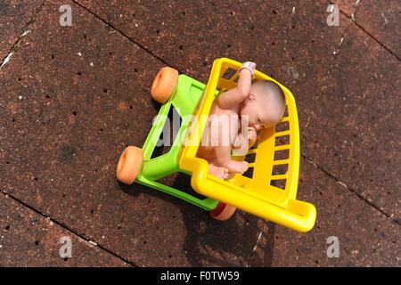Des Kindes Spielzeug Kunststoff Baby in einem Spielzeug Kunststoff Einkaufswagen. - Stockfoto