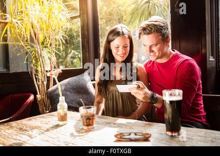Paar genießt trinkt Blick auf Smartphone zusammen - Stockfoto
