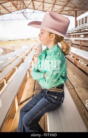 Mädchen tragen Cowboyhut auf Bank mit Armen gefaltet, Porträt - Stockfoto