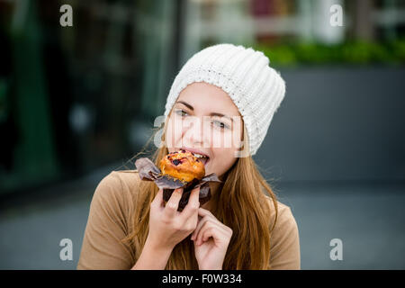 Junge Frau - Teenager im GAP Muffin in der Straße im Freien essen - Stockfoto
