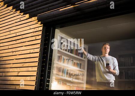 Mann mit Smartphone Blick aus Fenster zu Hause, Tokavaig, Isle Of Skye, Schottland