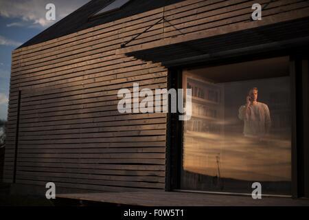 Mann mit Smartphone Blick aus Fenster zu Hause, Tokavaig, Isle Of Skye, Schottland - Stockfoto