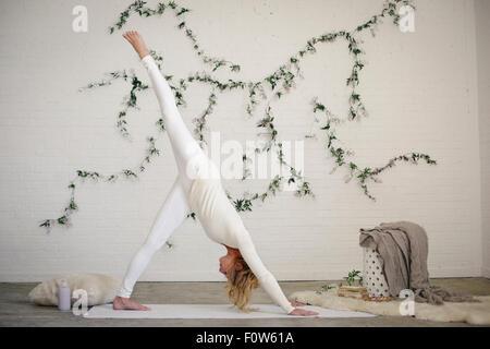 Eine blonde Frau in einem weißen Trikot und Leggings, auf eine weiße Matte in einem Raum stehen, bücken, hob ihr - Stockfoto