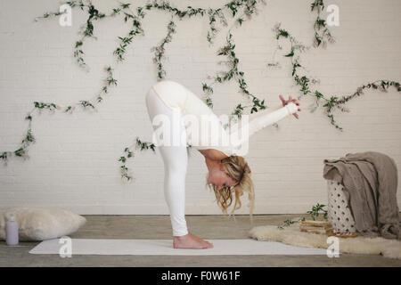 Eine blonde Frau in einem weißen Trikot und Leggings bücken, Strecken. Eine Schlingpflanze Pflanze an der Wand hinter - Stockfoto