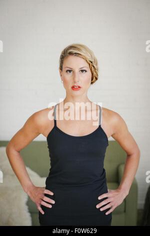 Eine blonde Frau in einem schwarzen Trikot stehen in einem Raum, machen Yoga, ihre Hände in die Hüften, in die Kamera - Stockfoto