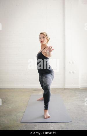 Eine blonde Frau in einem schwarzen Anzug und Leggings biegen Sie ihre Knie in einem Ausfallschritt mit ihren ausgestreckten - Stockfoto
