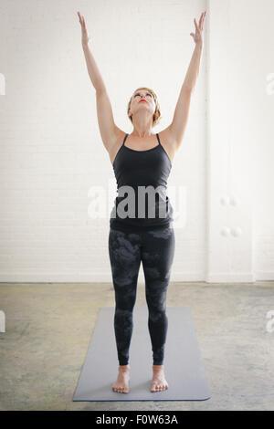 Eine blonde Frau in einem schwarzen Trikot und Leggings, stehend auf einer Yogamatte in einem Raum, machen Yoga, - Stockfoto