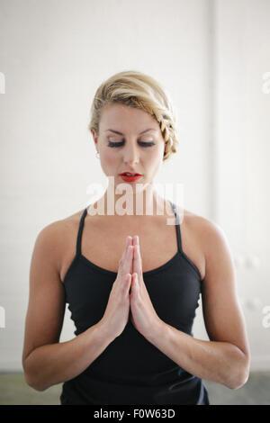 Eine blonde Frau in eine schwarze Trikot beim Yoga, stehen mit geschlossenen Augen und ihre Hände zusammen. - Stockfoto