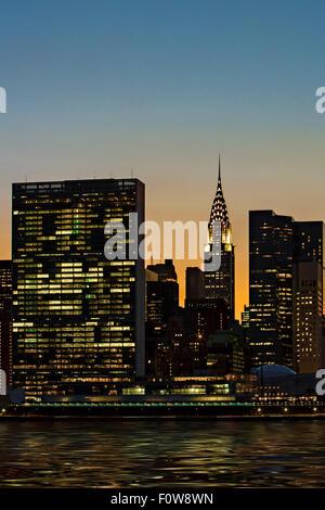 Die untergehende Sonne hinter dem Chrysler Building und das UN-Gebäude in New York City vom Gantry Plaza State Park - Stockfoto