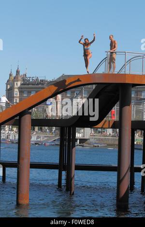 Girl Jumping von der Kalvebod Bølge, kalvebod Wellen oder Wave, im inneren Hafen von Kopenhagen. Tapferkeit Turm - Stockfoto
