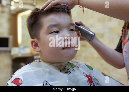 ein 7 jähriger Mischlinge junge immer eine Haar schneiden - Stockfoto