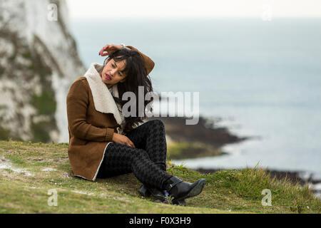 Junge Frau sitzt auf dem Rasen. Die weißen Klippen von Dover, Dover, Kent, Großbritannien - Stockfoto