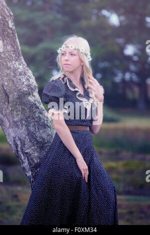 ein blondes Mädchen in einem floralen Dressl ist gegen einen Baum gelehnt. - Stockfoto