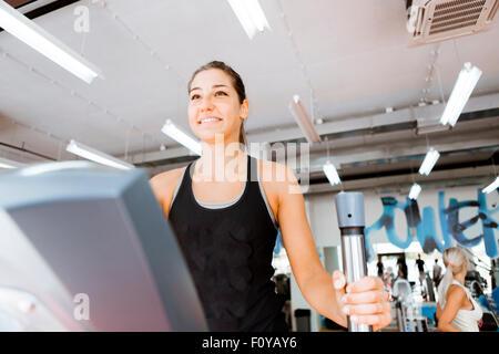 Junge passen Frau mit eine elliptische Trainer in einem Fitnesscenter und lächelnd - Stockfoto