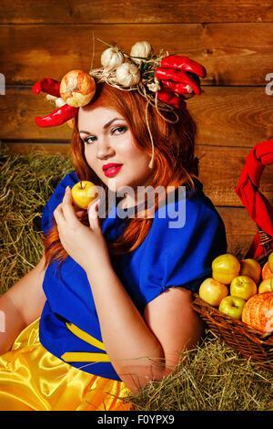Ein junges Mädchen hält einen Reifen Apfel in der Nähe von Korb mit einer Ernte von Gemüse und Obst. Erntefest. - Stockfoto
