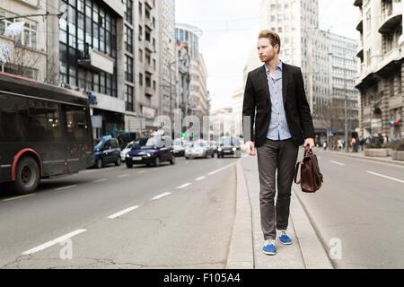 Gut aussehend Geschäftsmann zu Fuß die Insel auf einer belebten Straße - Stockfoto
