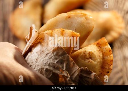 Fried kolumbianische Empanadas auf Holztisch. Herzhafte gefüllte Pasteten, auch bekannt als Pastell, Pastete oder - Stockfoto
