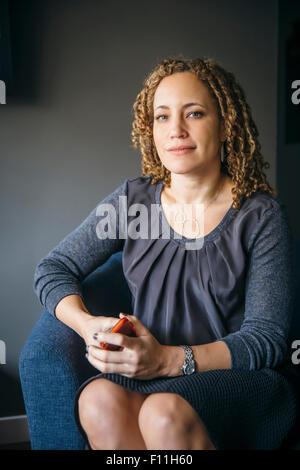 Gemischte Rassen Geschäftsfrau lächelnd in Sessel Stockfoto
