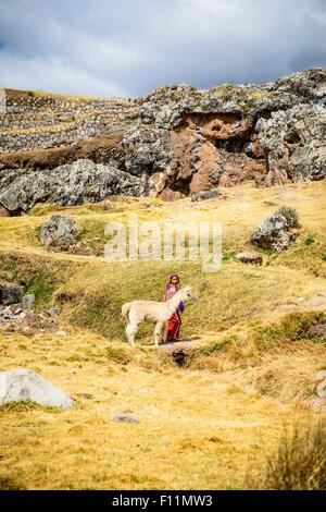 Hispanischen Mädchen zu Fuß Lamas in ländlichen Landschaft - Stockfoto