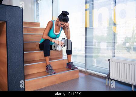 Müde Frau sitzt auf der Treppe mit Flasche Wasser im Fitness-Studio - Stockfoto