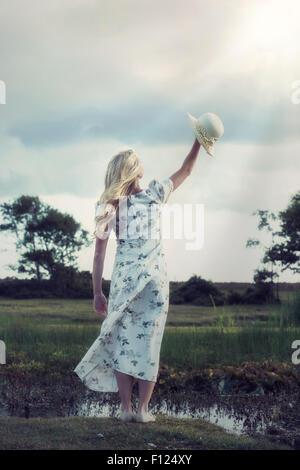 ein Mädchen mit einem Sonnenhut in der Abendsonne - Stockfoto