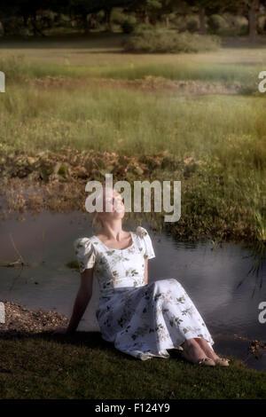 eine blonde Frau in einem geblümten Kleid sitzt an einem Teich, die Sonne genießen - Stockfoto