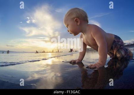 Sunset Beach Baby junge kriecht auf schwarzem Sand, Meer zum Schwimmen in Wellen surfen. Familie mit Kindern Urlaub - Stockfoto
