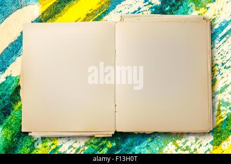 Alte leere Notebook auf farbigen Hintergrund geöffnet - Stockfoto