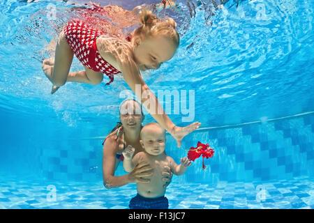 Junge Mutter lehrt, 10 Monate altes Baby Schwimmen - Tauchen mit fröhlichen Kind tief ins Blauwasser für eine rote - Stockfoto