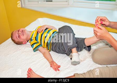 Kind legt zurück auf Bett lachen während immer seinen Fuß gekitzelt - Stockfoto