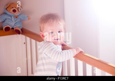 Jungen im Kindergarten aufwachen in seinem weißen Bettchen mit Teddy im Hintergrund. - Stockfoto