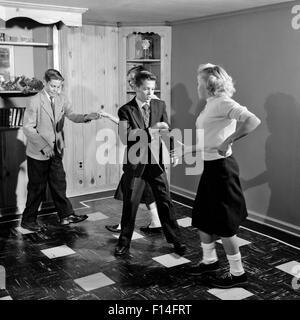 1950ER JAHREN VIER TEENAGER-JUNGEN UND MÄDCHEN TANZEN FEIERN - Stockfoto