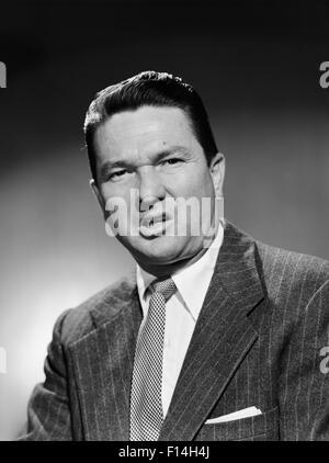 1950ER JAHREN GESCHÄFTSMANN IM ANZUG MACHEN LUSTIGE ERNSTHAFTE STIRNRUNZELN GESICHTSAUSDRUCK SPOTTEN EKEL WUT UNGLÜCKLICH - Stockfoto