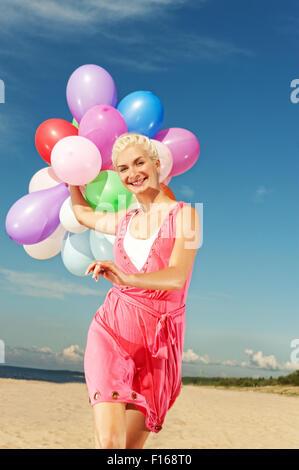 Glückliches Mädchen mit Luftballons laufen am Strand - Stockfoto