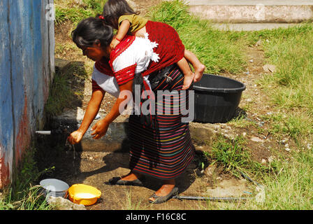 Guatemala, Aguacatan, Schule Mutter (Teresa de Leon Raymundo 32 Jahre mit Rita Aracely de Leon Raymundo 11 Monate) waschen Hände vor der Zubereitung Stockfoto