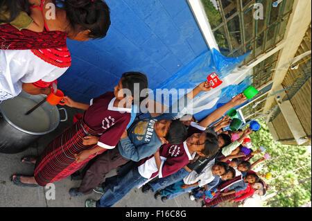 Guatemala, Aguacatan, Schule Mutter (Teresa de Leon Raymundo 32 Jahre mit Rita Aracely de Leon Raymundo 11 Monate) geben Snack an Schulkinder Stockfoto